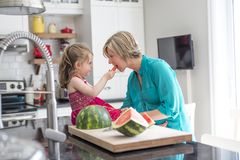 Mother and daughter cut watermelon in kitchen Royalty Free Stock Images