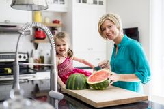 Mother and daughter cut watermelon in kitchen Stock Image