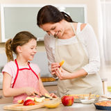 Mother and daughter cutting apples for pie Royalty Free Stock Photo