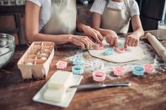 Mother and daughter cutting raw dough with cookie cutters stock images