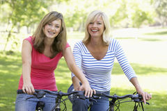 Mother And Daughter Cycling Through A Park Stock Photography