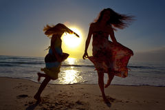 Mother and daughter dancing on beautiful beach. Royalty Free Stock Images