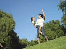 Mother and daughter (6-8) dancing on grass in park, girl holding MP3 player, surface level (tilt) Stock Photo