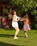 Mother and daughter dancing on grass at sunny day Stock Image