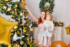 Mother and daughter decorate a Christmas tree. Royalty Free Stock Images