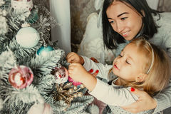 Mother and daughter decorate the Christmas tree Royalty Free Stock Images