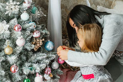 Mother and daughter decorate the Christmas tree Stock Images