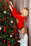 Mother with daughter decorate tree Royalty Free Stock Image