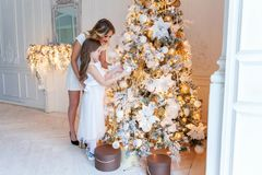 Mother and daughter decorating Christmas tree Stock Photo