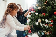 Mother and daughter decorating Christmas tree. Royalty Free Stock Image