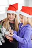 Mother And Daughter Decorating Christmas Tree Royalty Free Stock Image