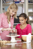 Mother And Daughter Decorating Homemade Cupcakes In Kitchen Royalty Free Stock Photos