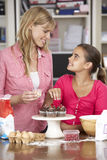 Mother And Daughter Decorating Homemade Cupcakes In Kitchen Stock Photo
