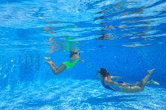 Mother and daughter dive in the swimming pool Royalty Free Stock Photo