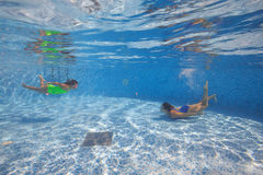 Mother and daughter dive in the swimming pool Royalty Free Stock Images
