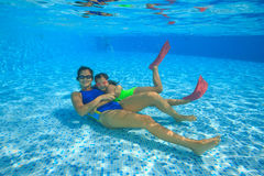 Mother and daughter dive in the swimming pool. Mother with her little daughter dive under water in the pool Royalty Free Stock Image