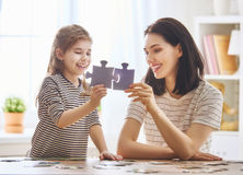 Mother and daughter do puzzles Stock Images