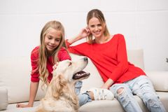 Mother and daughter with dog. Happy mother and daughter with dog sitting on sofa at home Stock Photography