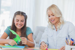 Mother and daughter doing arts and crafts together. At home in living room stock photography