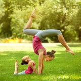 Mother and daughter doing exercise outdoors.