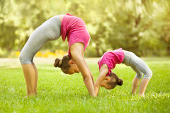 Mother and daughter doing exercise outdoors. Stock Photos