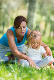 Mother and daughter doing exercise outdoors. Mother teaching her daughter how to do exercises Stock Images