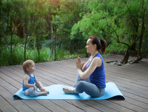 Mother and daughter doing exercise practicing yoga outdoors. Healthy lifestyle Royalty Free Stock Photo