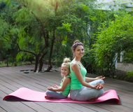Mother and daughter doing exercise practicing yoga outdoors. Healthy lifestyle Stock Image