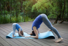 Mother and daughter doing exercise practicing yoga outdoors. Healthy lifestyle Royalty Free Stock Photography