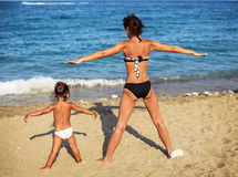Mother and daughter doing exercise. Royalty Free Stock Image