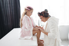 Mother and daughter doing hair and manicures Royalty Free Stock Images