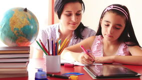 Mother and daughter doing homework on digital tablet stock footage