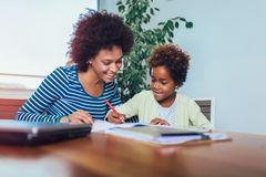 Mother and daughter doing homework learning to calculate stock images