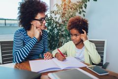 Mother and daughter doing homework learning to calculate royalty free stock photo
