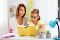 Mother and daughter doing homework together royalty free stock photo