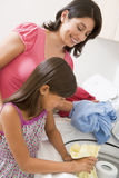 Mother And Daughter Doing Laundry Stock Photo