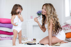 Mother and daughter doing makeup sitting on the bed in the bedroom Royalty Free Stock Images