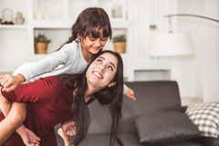 Mother and daughter doing piggyback in funny gesture emotion at home. Young sister playing with girl in good relationship royalty free stock image