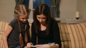 Mother and daughter doing a school homework assignment. Mom helps to deal with it. stock video footage