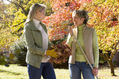 Mother and daughter doing yard work in autumn Royalty Free Stock Photo
