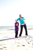 Mother and daughter doing yoga. Mother helping baby do yoga at the beach Royalty Free Stock Photography