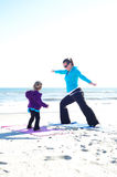 Mother and daughter doing yoga. Mother and baby doing yoga at the beach Royalty Free Stock Photography
