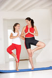 Mother and daughter doing yoga. Smiling at eachother Royalty Free Stock Image