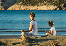 Mother and daughter doing yoga exercise on the beach.  Royalty Free Stock Images