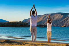 Mother and daughter doing yoga exercise on the beach Stock Images