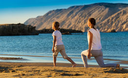 Mother and daughter doing yoga exercise on the beach Stock Photos