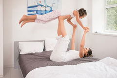 Mother with daughter doing yoga exercise in bed. Young mother and daughter gets up and doing morning yoga exercises in bed. Healthy lifestyle concept Stock Photo