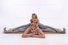 Mother daughter doing yoga exercise,fitness family sports, sports paired woman sitting on the floor stretching his legs apart in. Mother daughter doing yoga stock photography