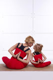 Mother and daughter doing yoga exercise, fitness, gym sports pai. Mother and daughter doing yoga exercise, fitness, gym wearing the same comfortable tracksuits Stock Photo