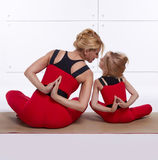 Mother and daughter doing yoga exercise, fitness, gym sports pai Royalty Free Stock Images